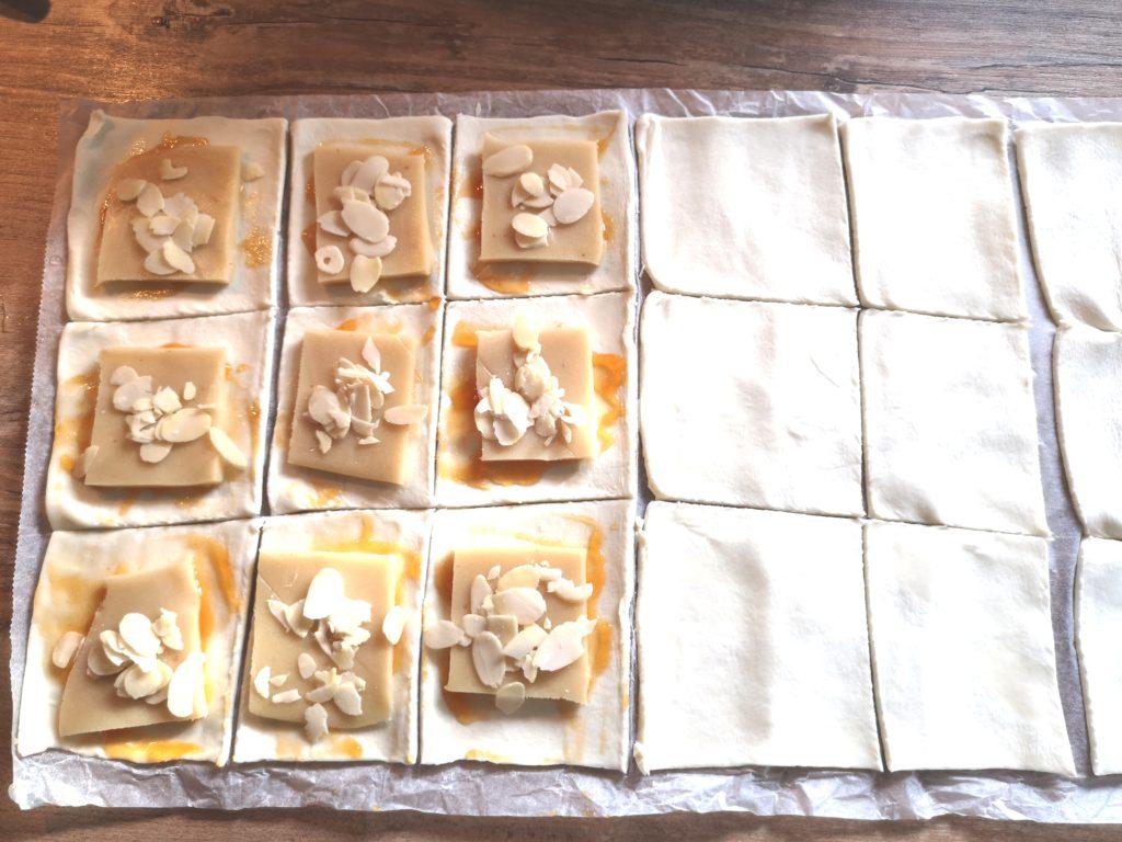 Marzipan Blätterteig Taschen: Marzipan, Aprikosenmarmelade und MAndelblätter auf dem Teig verteilen