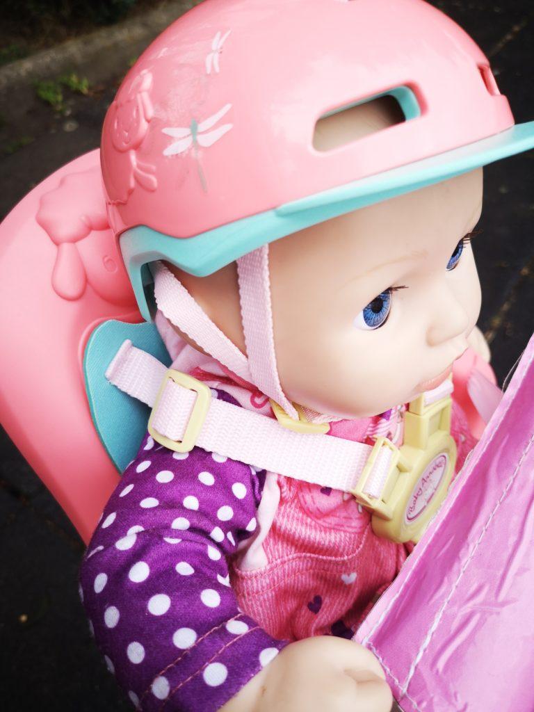 mit helm und fahrradsitz mit der baby annabell unterwegs